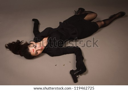 Detective scene imitation. Woman in a black suit with gun lying on the floor