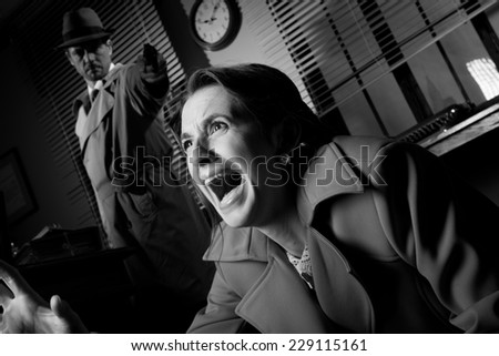 Detective standing in the dark and pointing a gun to a screaming woman. - stock photo