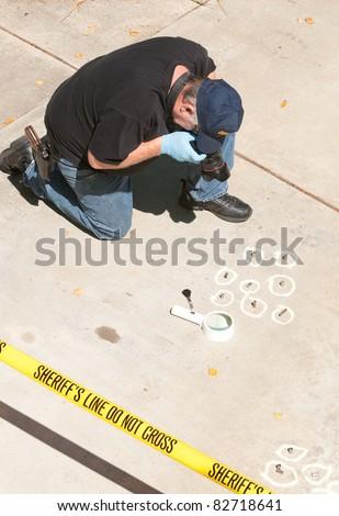 Detective studying a crime scene taking photographs - stock photo