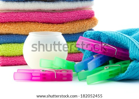 detergent ball, clothes pegs and a pile of towels isolated - stock photo