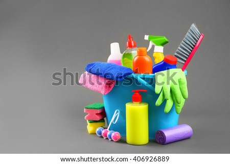 Detergent bottles and cleaning supplies in a bucket - stock photo