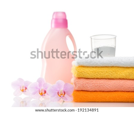 Detergent for washing machine in laundry with towels and flower in the white background. - stock photo