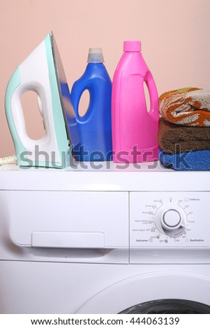 detergent, towels and a washing machine with a key point in the life of a plain background