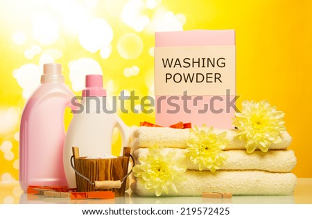 Detergent with washing powder and towels on yellow background - stock photo