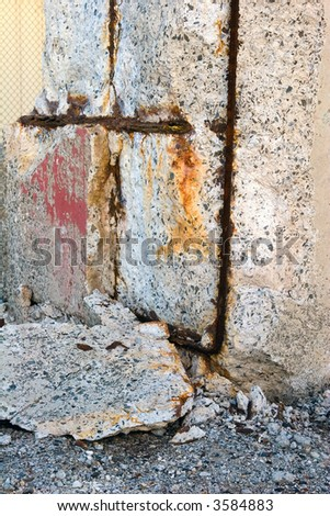 Deteriorating concrete block showing the rusting rebar inside - stock photo