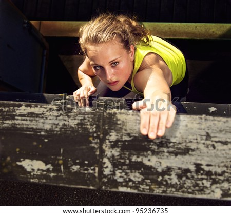 Determination on the face of a traceur climbing the wall of a high industrial building while demonstrating parkour - stock photo