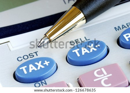 Determine the tax and the cost with a calculator - stock photo