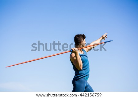 Determined athlete about to throw a javelin in the stadium
