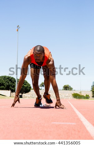 Determined athlete on a starting block about to run - stock photo