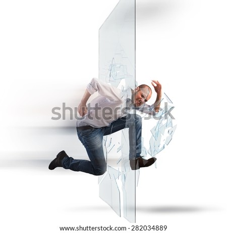 Determined businessman runs and breaking a glass - stock photo