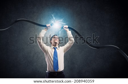 Determined businessman tearing electricity cable with hands - stock photo