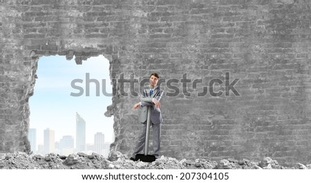 Determined businessman with big hammer in hands