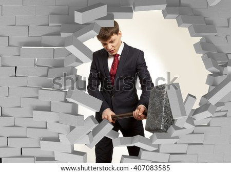 Determined businessman with hammer in hands