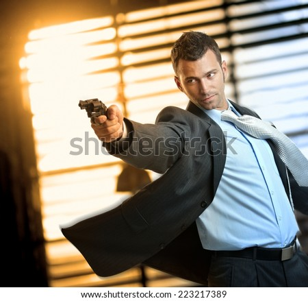 Determined caucasian action hero wearing suit and tie holding gun in hand. Standing, moving, aiming with revolver, inspector, cop, police, policeman, indoor, thriller, crime. - stock photo