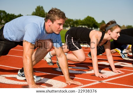 Determined competitors at the starting line.  Selective focus on first runner. - stock photo