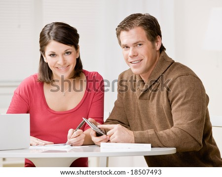 Determined couple using calculator to pay monthly bills - stock photo