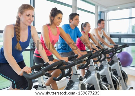 Determined five people working out at class in gym