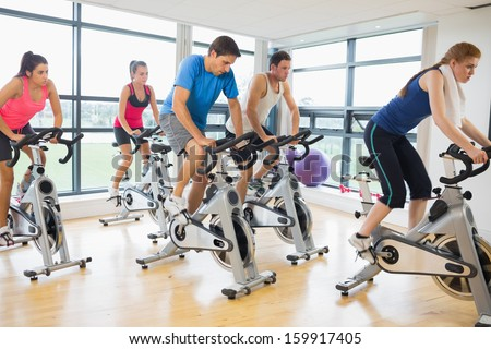 Determined five people working out in gym - stock photo