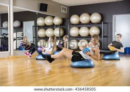 Determined Friends Exercising With Medicine Ball In Gym - stock photo