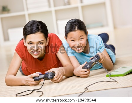 Determined friends having fun using video game controllers to play exciting video game - stock photo
