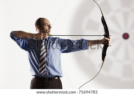 Determined handsome businessman aiming at target with bow and arrow, isolated on white background. - stock photo