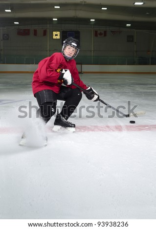 Determined Hockey Player Sprays Ice as he Makes Sharp Stop on Skates - stock photo