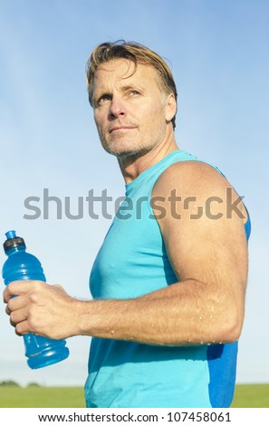 determined looking sportsman holding a water bottle in his hand. - stock photo