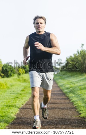 determined looking sportsman running in the park. - stock photo