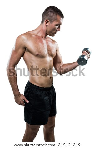 Determined shirtless athlete working out with dumbbell against white background