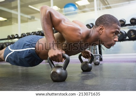 Determined shirtless muscular man doing push ups with kettle bells in the gym - stock photo