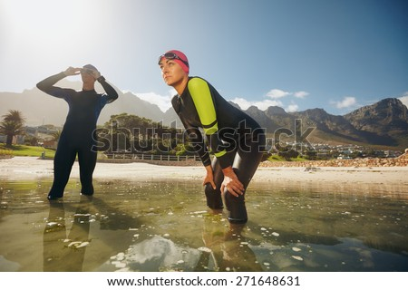 Determined sports persons standing in water getting ready for competition. Triathletes in wet suits preparing for triathlon. - stock photo