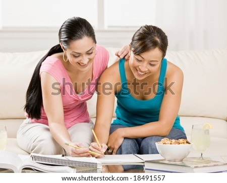 Determined student with text books helping friend do homework in livingroom - stock photo