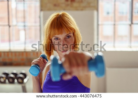 Determined woman lifting weights in a gym stretching her hand with a dumbbell towards the camera, focus to her face - stock photo