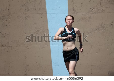 Determined woman runs for a healthy lifestyle. - stock photo