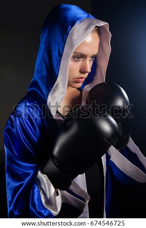 Determined woman wearing boxing gloves in fitness studio