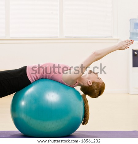 Determined woman working out on exercise ball in health club