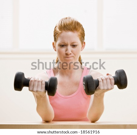 Determined woman working out with dumbbells in health club