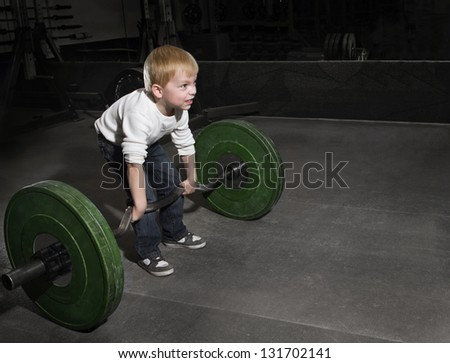 Determined Young Boy trying to lift Heavy weights - stock photo