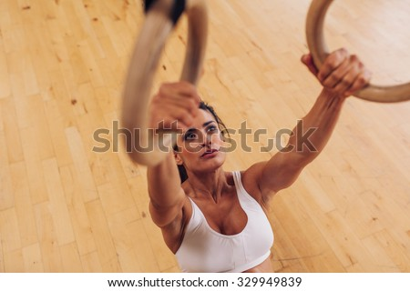 Determined young woman at gym. Muscular female athlete working out using gymnastic rings. - stock photo