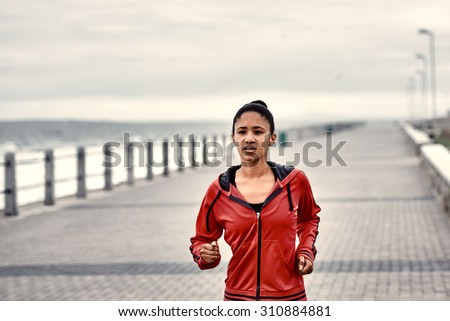 Determined young woman busy jogging along the ocean side on the promenade running until she no longer can - stock photo