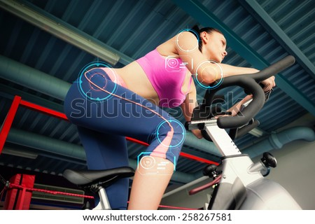 Determined young woman working out at spinning class against fitness interface - stock photo
