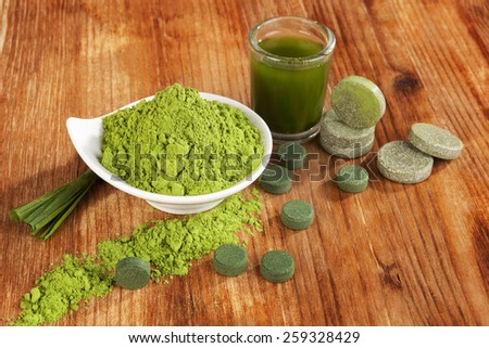 Detox. Chlorella pills, wheat grass powder and green drink in glass on brown wooden background. Natural alternative medicine, weight loss and detox. - stock photo