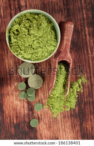 Detox. Chlorella, spirulina and wheatgrass ground and pills with wooden spoon on brown wooden background, top view. Alternative medicine. - stock photo
