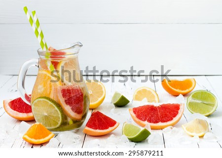 Detox citrus infused flavored water. Refreshing summer homemade cocktail with lemon, lime, orange and grapefruit - stock photo