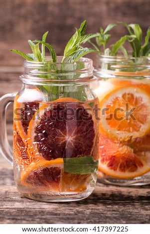 Detox citrus infused flavored water. Refreshing summer homemade cocktail with lemon, lime, orange and blood orange - stock photo