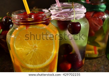 Detox fruit infused flavored water. Refreshing summer homemade cocktail. Cranberry and orange with mint.  Sweet cherry and  mint. Strawberry and kiwi with mint. - stock photo