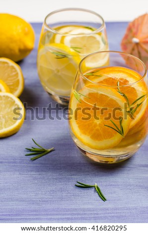 Detox fruit infused flavored water. Refreshing summer homemade cocktail with lemon and orange - stock photo
