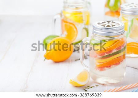 Detox fruit infused flavored water. Refreshing summer homemade lemonade cocktail Cleanse body and burn fat Copy space  - stock photo