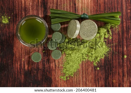 Detox. Green food supplements chlorella, wheat grass and spirulina pills, ground powder, grass blades and green drink on brown wooden background, top view. - stock photo