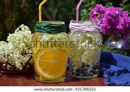 Detox infused flavored water in the glass jars. Light, refreshing drinks made with fresh seasonal  ingredients. Elderflower, berries of honeysuckle and orange slices. - stock photo
